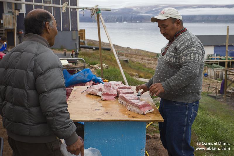 Chasseurs se partageant de la viande de baleine